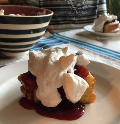 A slice of savarin topped with cherry compote and freshly whipped cream.